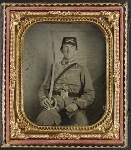 Private David M. Thatcher of Company B, Berkeley Troop, 1st Virginia Cavalry Regiment, in uniform and Virginia sword belt plate with Adams revolver and cavalry sword. 1861-1865. Library of Congress.